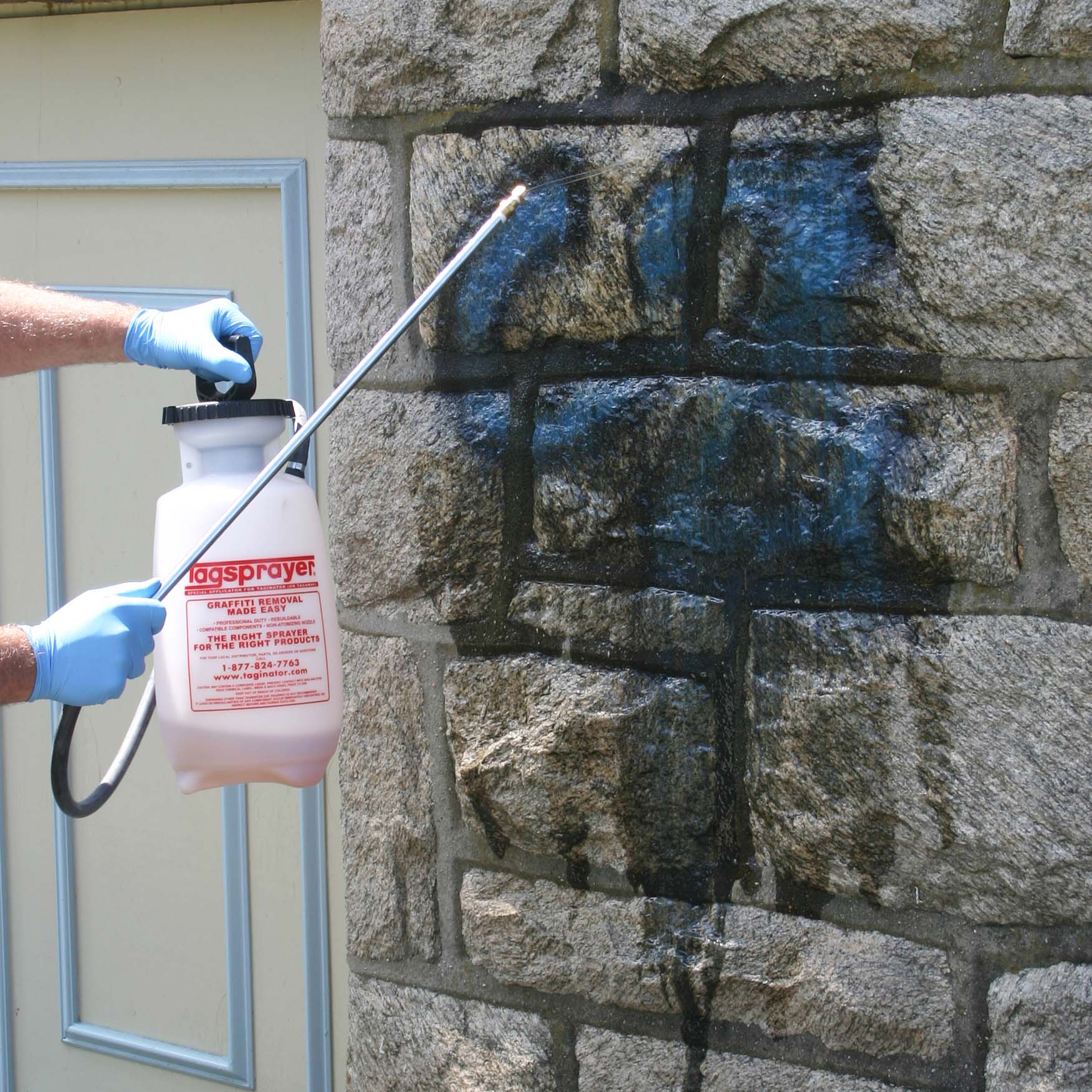 a contractor applying taginator graffiti removal to a brick wall